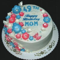 49Th Birthday White textured buttercream decorated with blue, pink and white gumpaste flowers with pearl centers and butterflies.