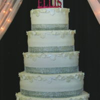 Bling, Lace & Blossoms Tiers are covered with white buttercream and bling ribbon borders. White fondant lace and blossoms with pearl centers form a top border...