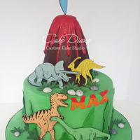 "Dinosaurs And Volcano Dinosaurs are edible images mounted on fondant. Melted red compound chocolate ""lava""."