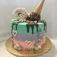 Ice Cream Drip Cake Ice cream drip cake with donuts and candy.