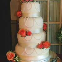 Pearl Drapes And Coral Roses Tiers are covered with white buttercream and white ribbon borders. Pearl drapes decorate each tier with coral rose accents. A double heart...