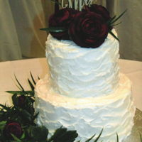 "Rustic Buttercream And Roses White rustic textured buttercream decorated with egg plant roses and a ""Mr. & Mrs."" topper."