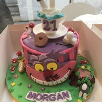 Alice In Wonderland 8 inch 4 layer lemon cake with Cheshire Cat design topped with edible cup and saucer and Alice's legs