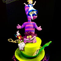 Alice In Wonderland Cake The Mad Hatter's hat cake stands tall with the Cheshire Cat doin' his thing on top. Alice falling as she does best, with the...