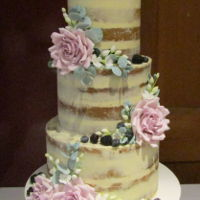 Dirty Iced Naked Wedding Cake Dirty iced naked wedding cake with sugar flower and leaves and fresh fruit
