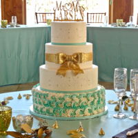 Elegant Sparkling Gold And Tiffany Blue Accents On Buttercream All buttercream design with stenciled accent, tiffany blue swirled buttercream and a sparkling gold fondant bow.