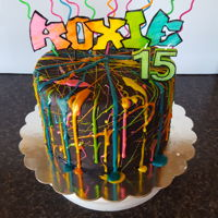 Graffiti Splatter Triple layer 8 inch cake covered with black fondant and royal icing splatters. Name topper is hand cut/painted fondant.