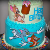 Tom & Jerry Birthday Cake Vanilla-almond cake frosted in vanilla-almond buttercream, decorated with 2D drawings of Tom and Jerry with a fondant topper of the two....
