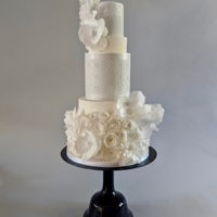 White Wedding Cake With Wafer Paper Flowers A bounty of wafer paper flowers adorn this rather simple white wedding cake. I love the white on white look. Do you?