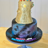 Avengers Infinity War Thanos Cake Carved Thanos Gauntlet Cake on top of a Galaxy Cake. Thanos' Gauntlet was painted gold with lustre dust and Vodka. Galaxy was sponged...