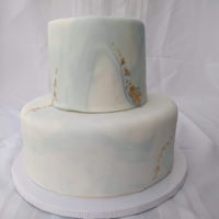 Elegant Wedding Cake Two tiers, 10 inch and 6 inch, vanilla cake with cream cheese frosting, marbled fondant with edible gold leaf accents.