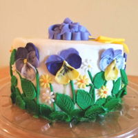 "Fondant Pansies 7"" cake with fondant pansies, leaves, bow and banner"