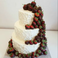 Strawberry Love Rustic swiss meringue wedding cake decorated with chocolate strawberries.