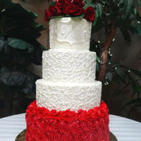 Filigree And Rosettes Wedding Cake Six, Eight, Ten and Twelve inch rounds in buttercream with hand-piped filigree and rosettes and fresh Roses on top.