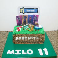 Fortnite chocolate cake covered in butter cream , decorations are gumpaste, characters are paper prints