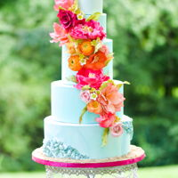Living Coral Wedding Cake A fun tropical-themed Living Coral wedding cake with bold sugar flowers, edible sea-shell bas-relief and a cool blue color palette.