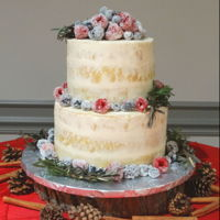 Naked Wedding Cake With Berries Eight and six inch rounds in sparse 'naked' icing with sugar frosted berries.