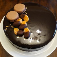 Orange/dark Chocolate Entremet Cake Nine inch Entremet Cake with layers of dacquoise, cremeux, jaconde, jelly, and mousse, all encased in a dark chocolate mirror glaze and...