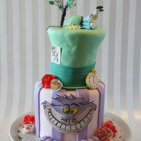 Alice In Wonderland Cake Six inch round with Four inch top hat covered in fondant with gumpaste flowers and decorations.