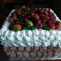 Birthday Cake Two layer vanilla and chocolate cake covered with whipping cream and decorated with fresh fruits. Grape and strawberries