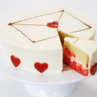 Easy Valentine's Day Cake! Simple round cake covered with buttercream and decorated with fondant heart cut outs, perfect for valentines day!