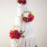 Lady In Red This wedding cake features a white, red, and gold color palette. The cake is adorned with fondant lace and accented with couture sprinkle...