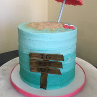 Ombré Beach Cake! Textured buttercream with red velvet layers. Fondant balloon and sandals. Sand is ground up Graham crackers. The sign is popsicle sticks...