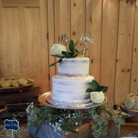 Semi-Naked Wedding Cake Butter cake filled with Bavarian cream. Iced with buttercream. 4 mm Silver dragees placed on the border. Placing of fresh roses and topper...