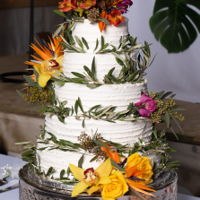 Tropical Wedding Cake 5 tier cake adorned with fresh flowers. Flavors included: Chocolate Fudge filled with white chocolate mousse, French Vanilla filled with...