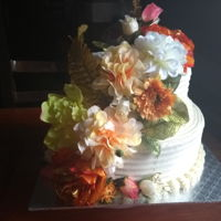 Wedding Cake Two tier vanilla butter cake with buttercream icing and decorated with artificial flowers