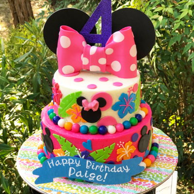 "Minnie Mouse Luau 8""-6"" tiered cakeStacked, filled, and iced in buttercream with fondant embellishments."