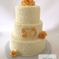 50Th Anniversary Cake 3 tier Buttercream iced cake. I made the roses out of modeling chocolate and dusted them gold. Thanks for looking!