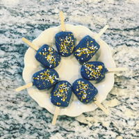 "Cakesicles Vanilla and buttercream ""dough"" hand-formed and dipped in Navy candy melts. Embellished with with white/gold sprinkles..."