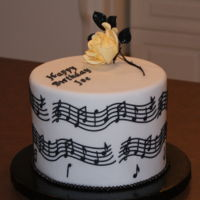 Musical Notes Cake This cake is a white cake covered with chocolate ganache, then with Carma fondant. The rose is made of gum paste.