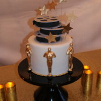 Oscar Cake The movie reels and Oscars are made with a mixture of gum paste and fondant. The cake is chocolate covered in ganache then fondant.