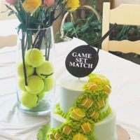 "Tennis Cake 8""and 6"" tiers stacked, filled and iced in buttercream. Chocolate and fondant tennis balls. Custom topper cut with..."