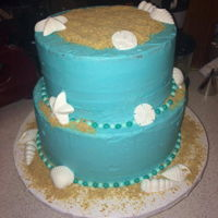 Baby Shower Cake This is a beach themed baby shower cake that I did, it is an amaretto cake with white chocolate buttercream. Shells are white chocolate....