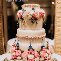 Maddy Wedding Cake 4-tier wedding cake with custom brooches and sugar flowers. Top three tiers are round shaped. Base tier is a petal-shaped tier to allow for...