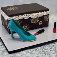 "Shoes And Makeup Cake 11""X7"" chocolate fudge cake with dark chocolate buttercream filling. Cake is paneled in fondant with airbrushed details. Fondant..."