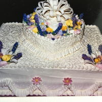 "Design For Many Occasions A 14""x4"" sq topped w/a 9""x4"" heart; all buttercream; Cornelli lace; fondant loop bows; flowers air..."
