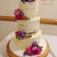 Dirty Iced Wedding Cake Dirty iced wedding cake with fresh fruit and flowers