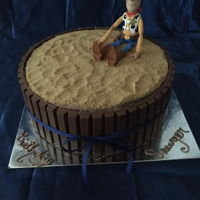 Toy Story Cake Woody sitting on top of a dirt covered cake