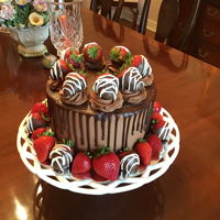 Chocolate Doberge Cake With Strawberries Five layers of vanilla butter cake with chocolate pudding filling. Frosted with chocolate buttercream and ganache drip. Finished off with...