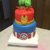 Super Hero Cake Vanilla cake with vanilla buttercream, covered in MMF. Hulk fist is RIce Krispie treat covered in white ganache & MMF.