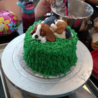 Granddaughters Birthday Cake, Puppy's Simple White Cake with buttercream layers and outer layer. Simple syrup on each layer. Puppy's are hand made using fondant.
