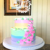 Pastel Rainbow Cake Two tiered rainbow stripe cake with cascading buttercream flowers.