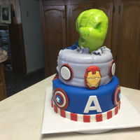 Super Hero Cake This a popular cake. 3rd one I've done this year. Vanilla cake covered in buttercream & MMF. Hulk fist is rice Krispie Treat...
