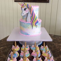 Unicorn Cake Topper Two tiered unicorn themed cake and cupcakes.