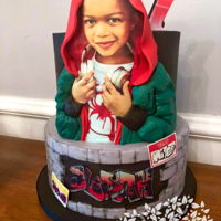 3D Photo Miles Morales Inspired Cake Cake inspired by Miles Morale Spiderman character with 3D details surrounding edible image photo on top tier. Graffiti and brick bottom...