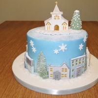 Snowy Winter Village Rich fruit cake soaked for a few weeks with extra brandy, marzipan and fondant. Used airbrush to spray blue. Made for Mom and Dad